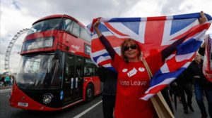 A campaigner wearing a Vote Leave t-shirt and holding a British Union Flag also known as a Union Jack stands on a Westminster Bridge near the Houses of Parliament in London U K Wednesday June 15 2016 The Brexit battle took to London s River Thames as boats supporting the Leave and Remain campaigns jostled for space while Irish rock star Bob Geldof harangued U K Independence Party leader Nigel Farage using a sound system Photographer Luke MacGregor Bloomberg via Getty Images